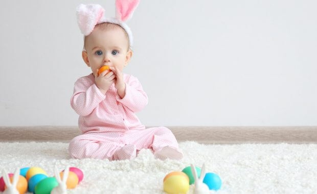 a baby sitting on safely cleaned carpet during easter