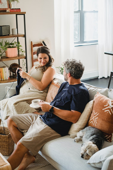 Wife and husband laying on the couch with their dog, relaxed knowing that their recently cleaned upholstery is helping with their allergies.